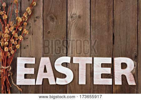 Easter Spelled In Wooden Letters With Bundle Of Willow Branches Over A Rustic Wood Background