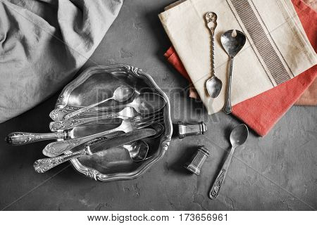 Set of silverware with napkins on grey background