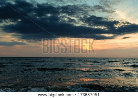 poster of late in the evening on the sea, dark, beautiful landscape with sea waves and dark sky with bright orange stripes, cloudy, skyline, night, vespertine, extramural, afterdark
