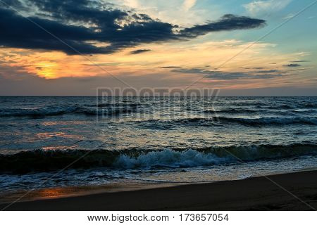 late in the evening on the sea, dark, beautiful landscape with sea waves and dark sky with bright orange stripes, cloudy, skyline, night, vespertine, extramural, afterdark