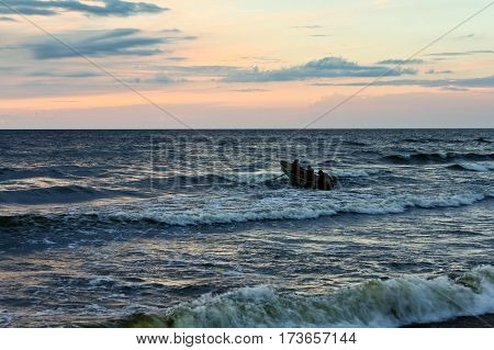 poster of late in the evening on the sea, dark, beautiful landscape with sea waves and dark sky with bright orange stripes, cloudy, skyline, night, vespertine, extramural, afterdark, a boat, few men three, wave