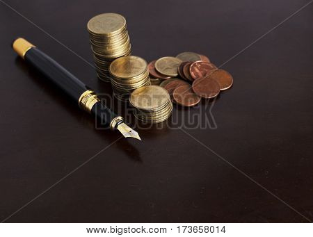 Business Fountain pen and coins stack for Finance concept