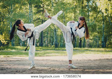 Gemini girl karate crossed their legs in the air outdoors