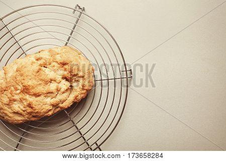 Tasty loaf of beer bread on metal stand