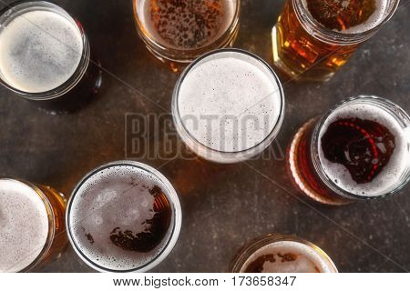 Glasses with beer on gray background