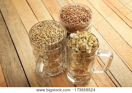 Glasses with wheat, hop and barley on wooden background