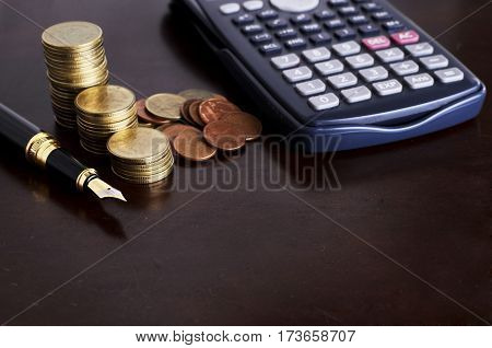 Fountain pen and calculator and coins for loan money concept