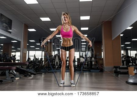 Fitness Beautiful Woman Execute Exercise With Expander In Gym