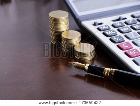 Fountain pen and Money coins stack and calculator for finance concept