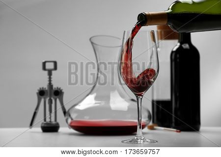 Pouring wine in glass on light background