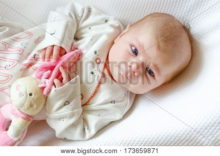 Cute adorable newborn baby againgst white background. New born child, little girl looking and crying at the camera. Family, new life, childhood, beginning concept.