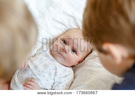 Two little kids boys with newborn baby girl, cute sister. Siblings. Brothers and baby playing with colorful toys and rattles together. Kids bonding. Family of three bonding, love.