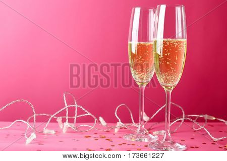 Glasses of champagne on pink background
