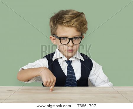 A Caucasian Boy Pointing Wooden Table Background Studio Portrait