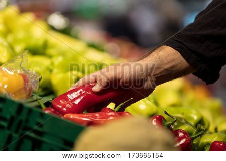 sale, shopping, food, consumerism and people concept - woman with basket buying bell peppers or paprika at grocery store.