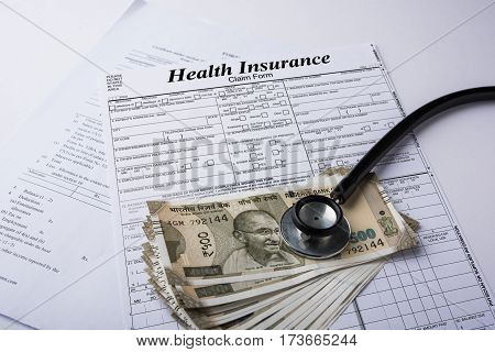 Health insurance form with indian money or currency notes of 500 and 2000 rupees and stethoscope concept for life planning