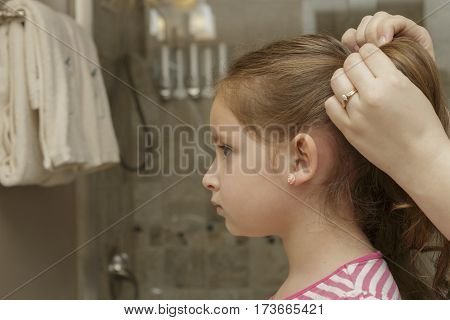 little girl getting her hair put in pigtails