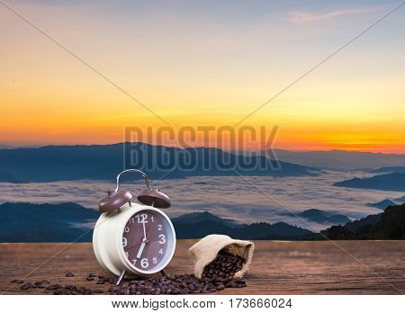 Alarm clock with coffee beans on wooden table with morning light background the nature mountain sunrise