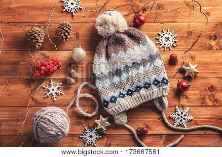 Christmas decorations and knitted hat on wooden background