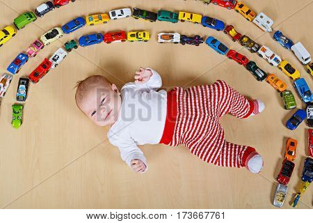 Cute little newborn baby playing with lots of toy cars indoor. Child wearing red clothes. Happy new born having fun at home or nursery. Big collection of different vehicles. Happiness game