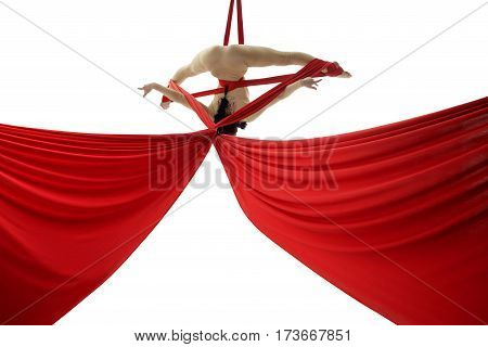 Young graceful woman perfoming exercises on aerial red cloth in studio