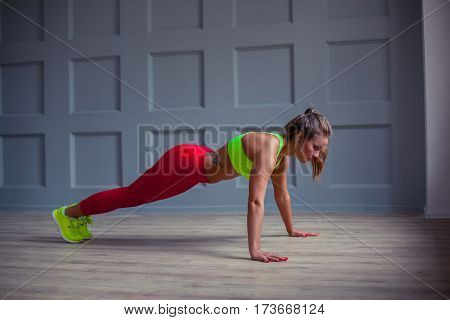 Beautiful fitness woman is doing push-ups in the gym