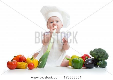 Little girl dressed in white chef hat and apron eats fresh onion. Child with vegetables: eggplant, popcorn, broccolli, peppers, zucchini, tomatoes over white