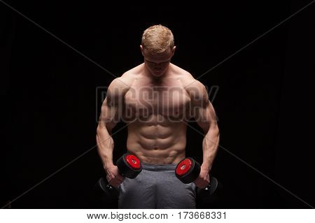 Handsome power man fitness-model with six packs is training with dumbbells, isolated on black background with copyspace.