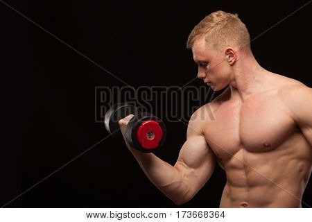 Athletic handsome man fitness-model is working out with dumbbell and showing his perfect body. isolated on black background with copyspace.