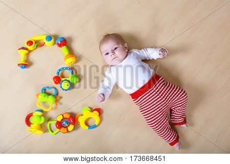 Cute adorable 2 month old baby playing with lots of colorful rattle toys. Newborn child, little girl looking surprised at the camera. Kid having fun. Family, new life, childhood, beginning concept