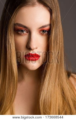 Glamour portrait of beautiful woman. Fashion shiny highlighter on skin sexy gloss lips make-up. Red lips. Portrait of beautiful young woman with long brown hair and bright make-up. Red eye shadow