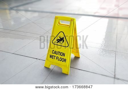 Yellow caution sign showing wet floor with blur background