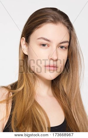 Young woman with blond hair no makeup. Nude makeup. The girl in a sports top Portrait of a beautiful young woman on a white background