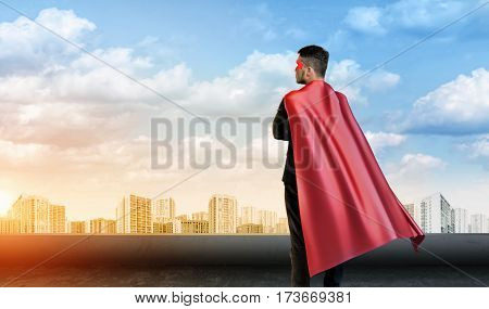 A businessman in super hero cape standing turned back on the sky background with cityscape below. Business hero. Confidence and success. New opportunities.