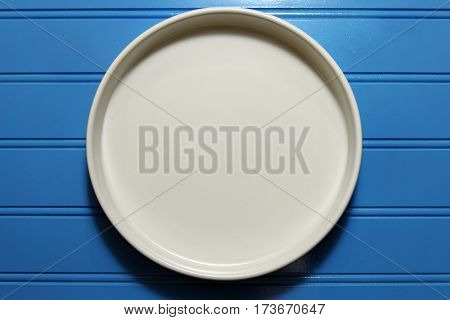 A round white plate on blue wooden background copy space