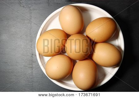 Top view of brown eggs in a white round plate on a black background