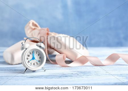 Alarm clock and pointe shoes on color wooden table