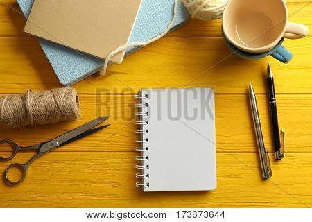 Composition with notebook, scissors, thread and cups on yellow wooden background