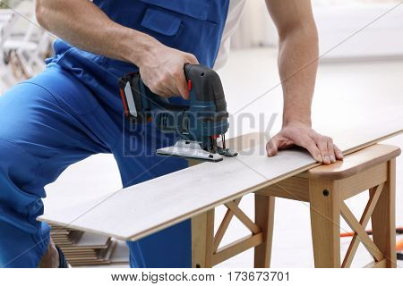 Man cutting laminate board with jigsaw