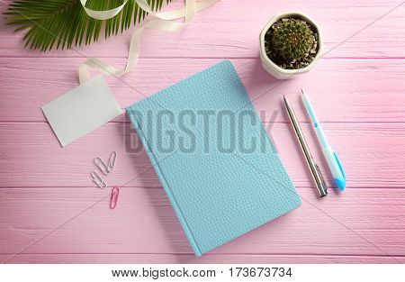 Beautiful notebook and cactus on pink wooden table
