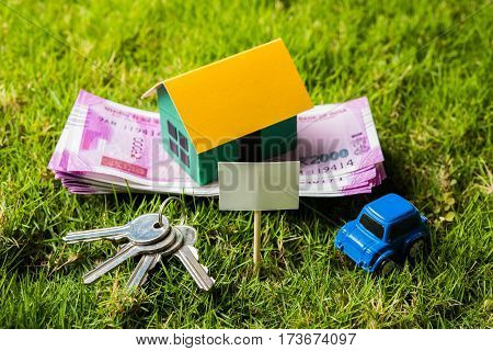 indian currency notes of rupees 100, 500 and 2000 in roll or stack with small home model, keys, toy car and calculator with blank board over green grass - home buying and finance concept in India
