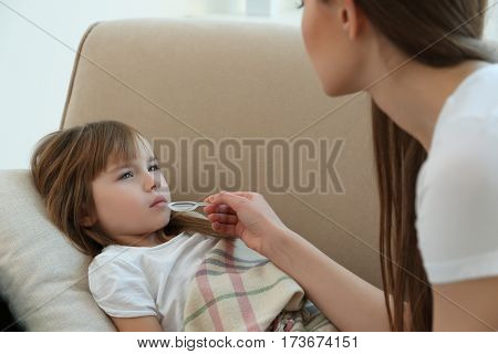 Mother giving her daughter medicines at home
