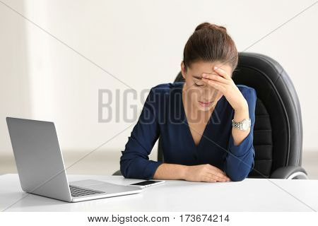 Tired young woman sitting in office