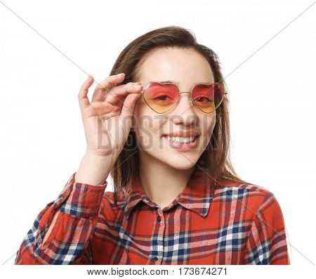 Beautiful young woman with heart-shaped glasses on white background