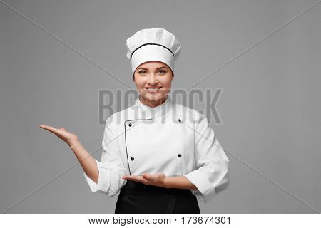 Portrait of young woman chef on light background