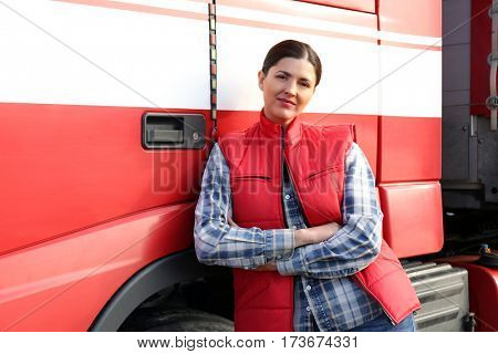 Young female driver near big modern truck outdoors