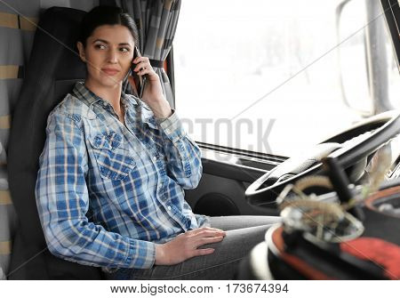 Young female driver talking by mobile phone while sitting in cabin of big modern truck