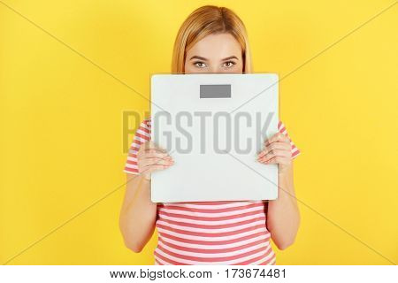 Beautiful pregnant woman holding scales on yellow background