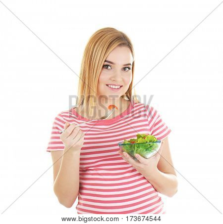 Young pregnant woman holding bowl with salad on white background