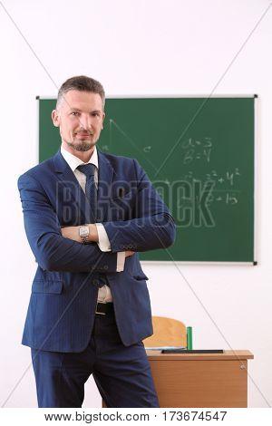 Handsome confident teacher in classroom